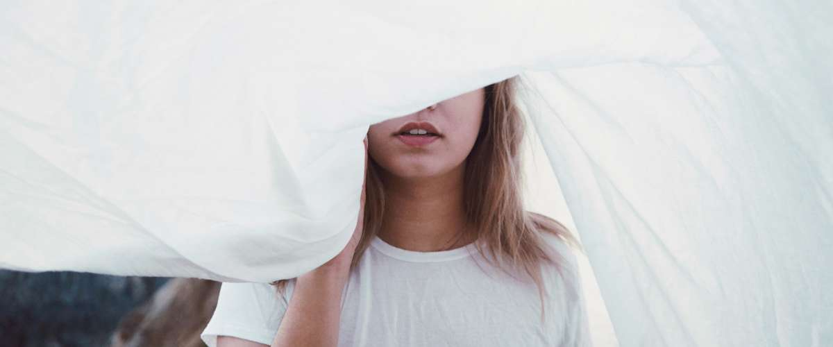 Young woman walking through sheets out to dry
