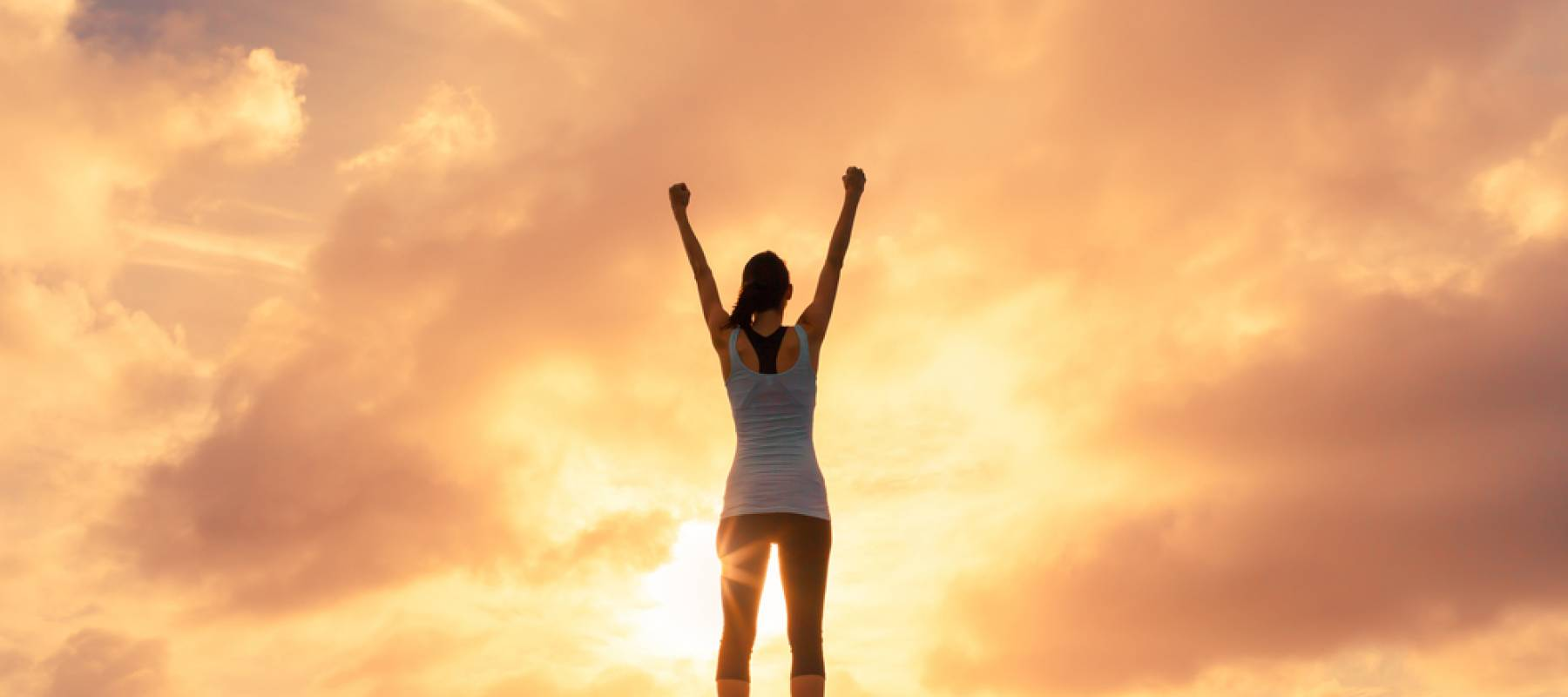 woman's silhouette, she is raising her arms in victory