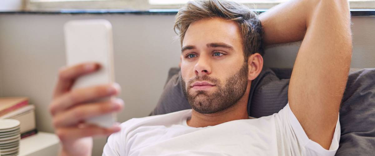 Handsome young man in pajamas using a cellphone while lying in bed in the morning