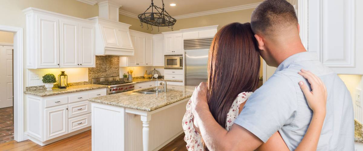 Young couple looking at beautifully renovated kitchen.