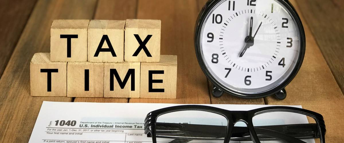 Tax-filling concept - 'Tax time' words on wooden blocks, pen, eyeglasses