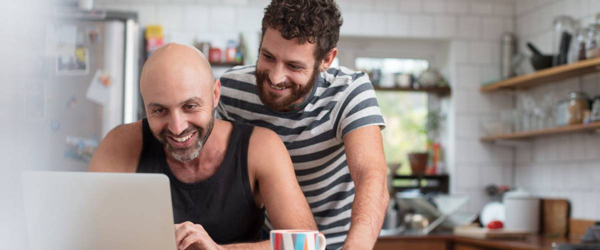 Gay couple using laptop in the kitchen
