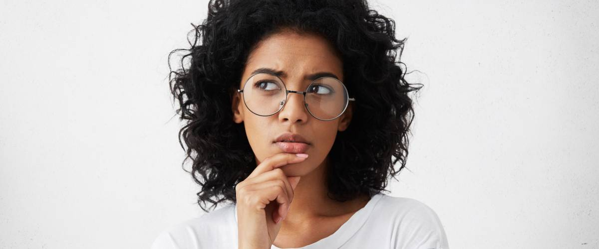 Isolated portrait of stylish young mixed race woman with dark shaggy hair touching her chin and looking sideways to make a decision