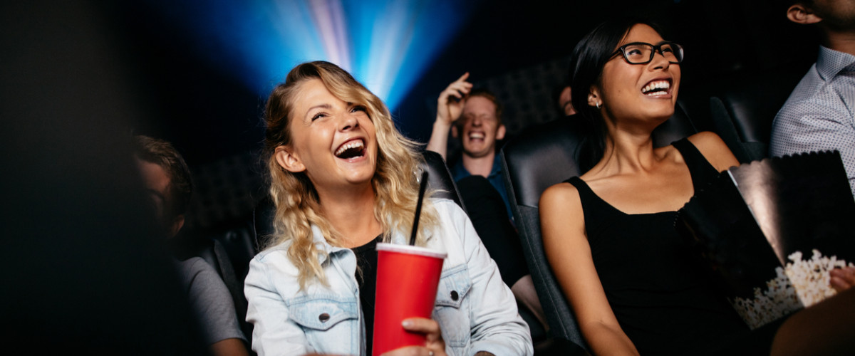 Young people laughing while watching film in movie theater