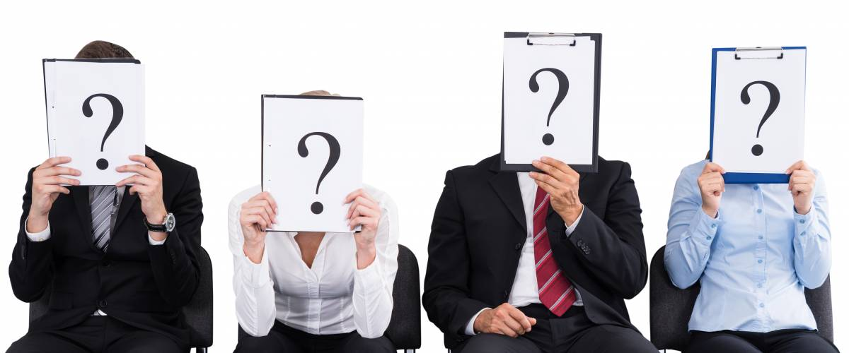 Business people holding clipboards with question marks over their faces