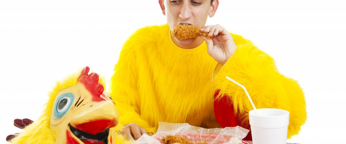 Young man taking a break from his job as the chicken mascot at a fast-food restaurant