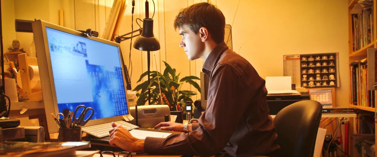 Young man working at the computer in his home office