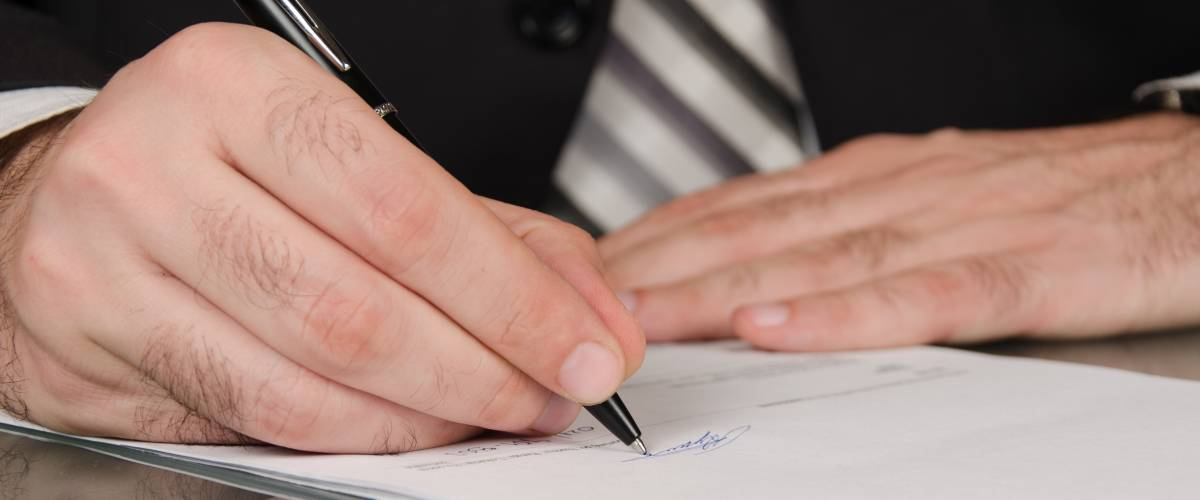 Businessman in a suit, signing legal document