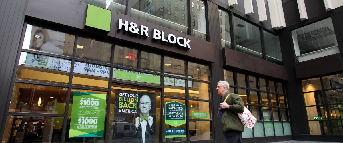 Man walking past H&R Block tax preparation office