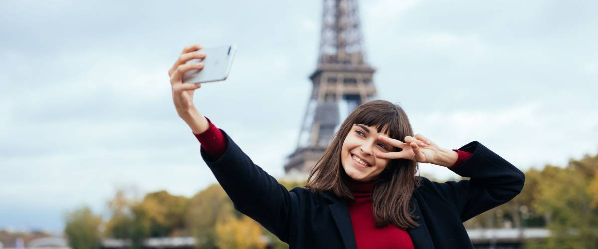Woman tourist at Eiffel Tower smiling and making travel selfie. Beautiful European girl enjoying vacation in Paris, France