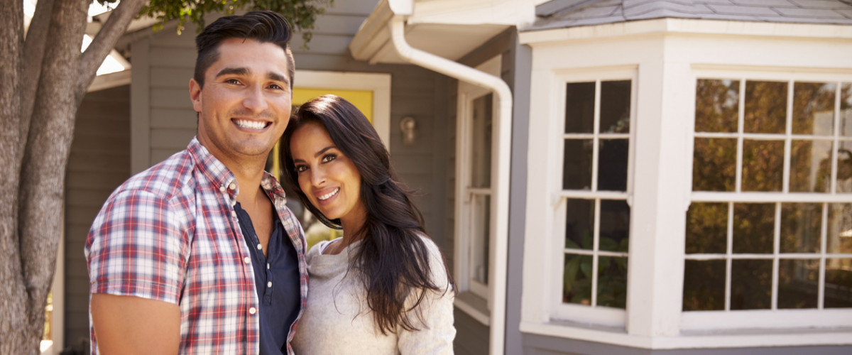 Portrait Of Couple Standing Outside Home