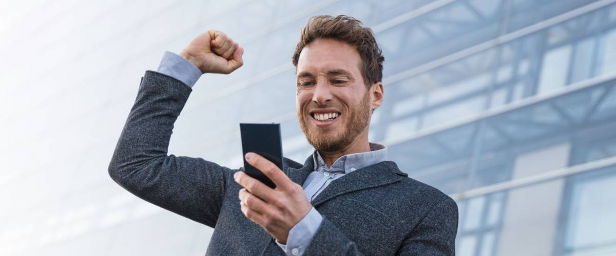 Success winner business man winning on cellphone app. Cheering businessman looking at smartphone online gaming challenge or work deal.