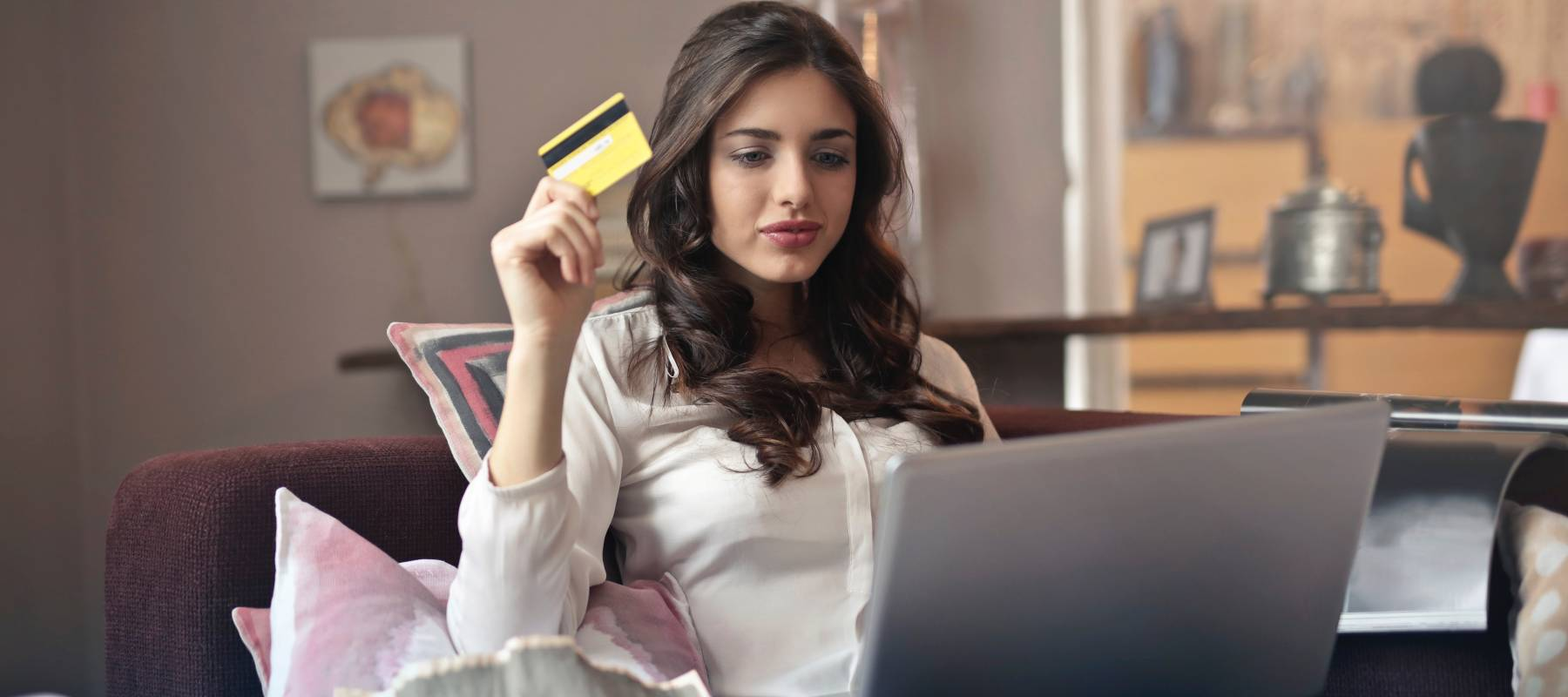 Woman holding credit card and looking at her laptop computer