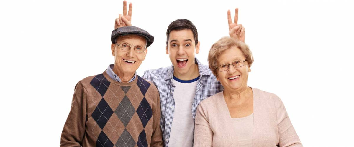 Young man pranking a mature man and woman with bunny ears isolated on white background