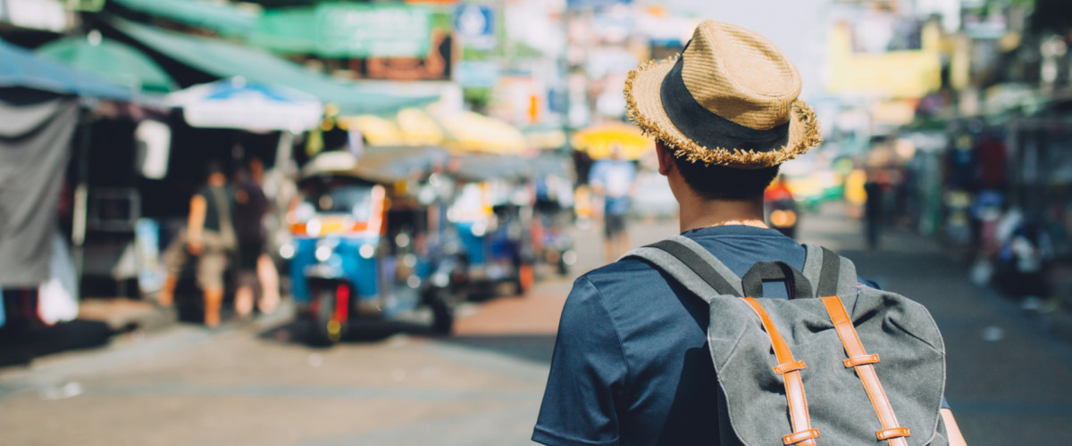 A young traveler walks through a market in Bangkok, Thailand wearing a backpack and a sun hat
