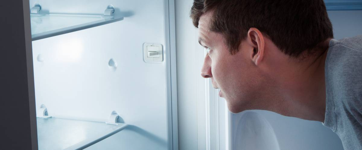 Man starting into an empty refrigerator