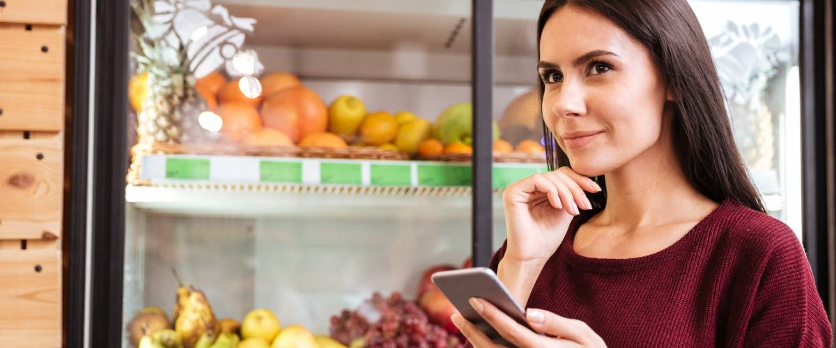Woman shopping in supermarket from a list on her smartphone