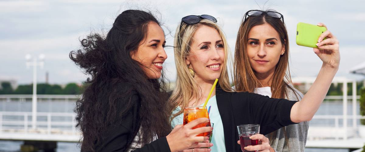 Three young women enjoying cocktails and taking a selfie