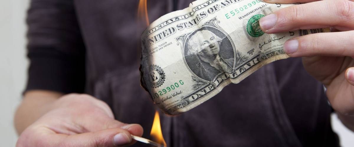Hands setting fire to a dollar bill