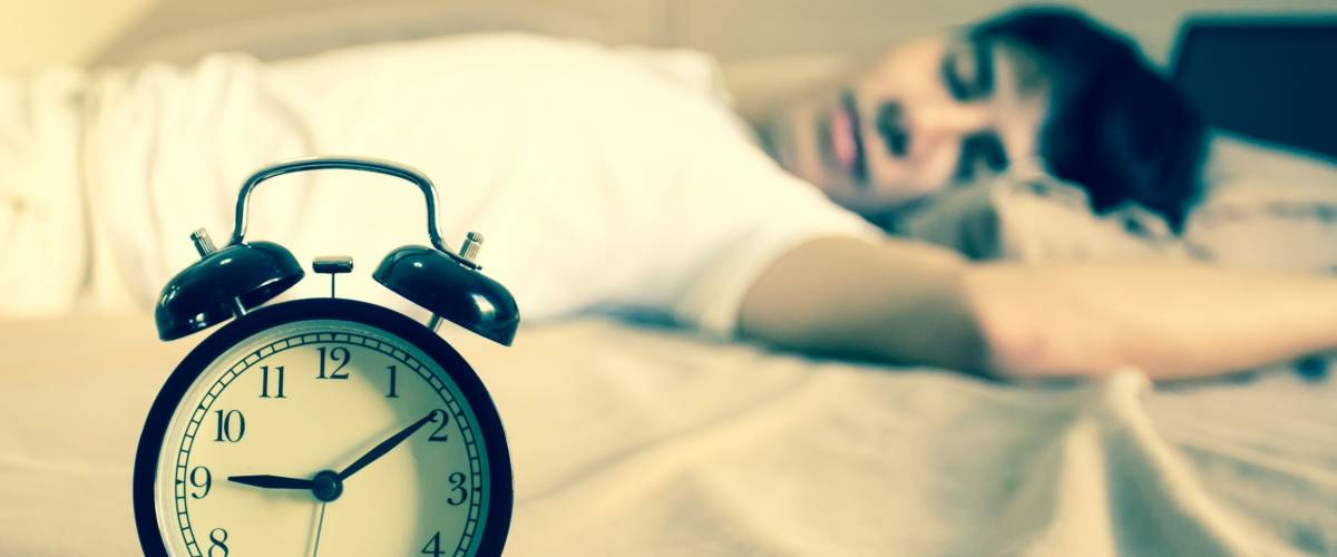 Man sleeping with alarm clock on morning.