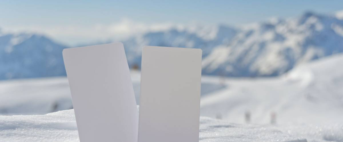 Two blank winter sport ski pass tickets with scenic background. Concept to illustrate winter sport admission fee
