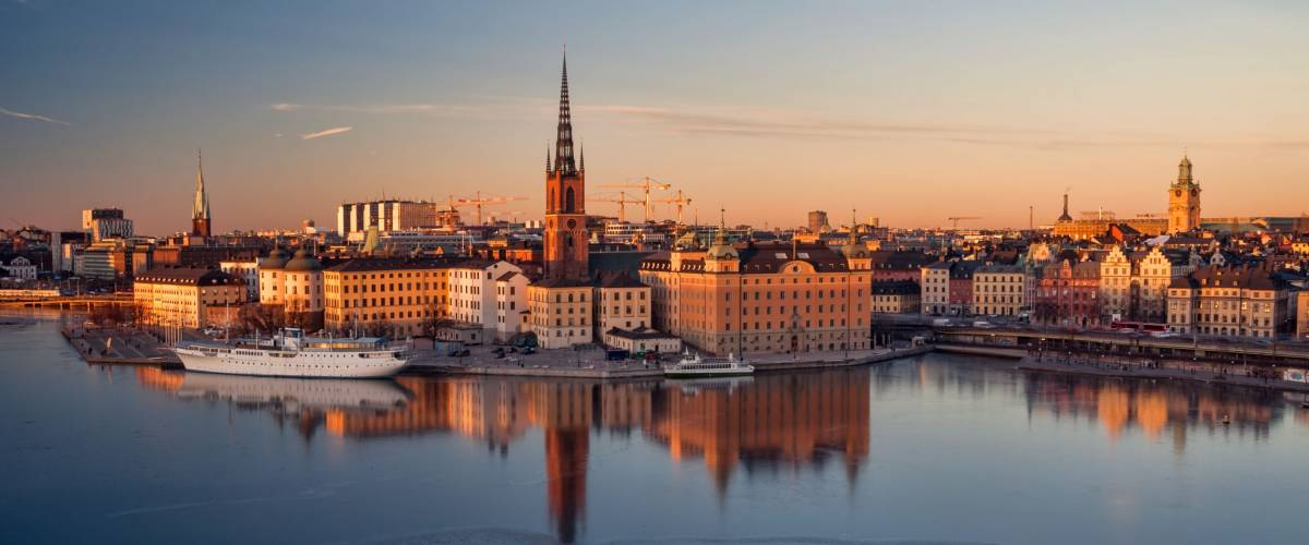 Panoramic overview of the Old Town of Stockholm from above. Historic buildings colored in warm tones by setting sun. Beautiful reflections in frozen water.