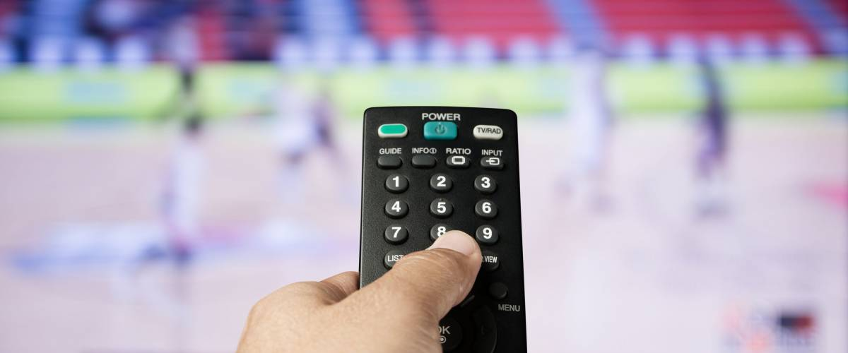 Hand of man holding remote control  TV on sport channel program background