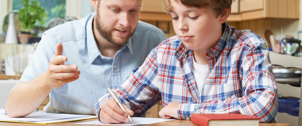 Male home tutor helping boy student with studies