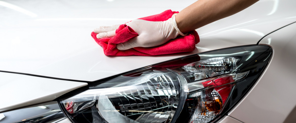 Car detailing cleaning a white car with a microfibre cloth and a white glove