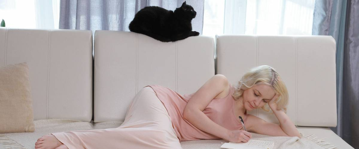 Woman alone, lying on the couch alone in the room. Beside her cat