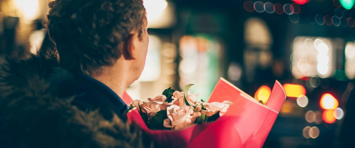 Man with bouquet of pink roses to take to a date.