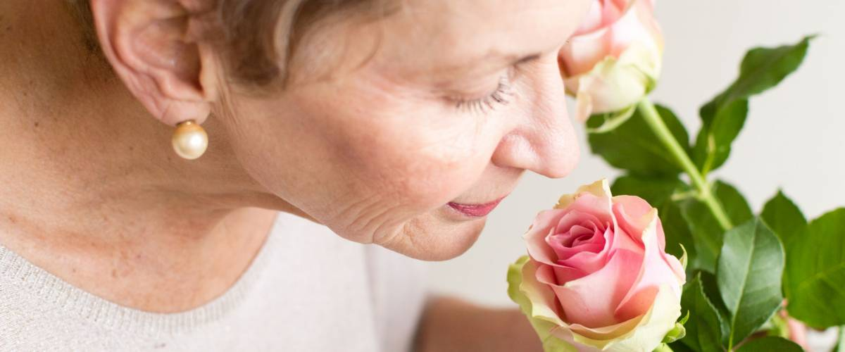 Older woman in beige top smelling pink rose (selective focus and close up)