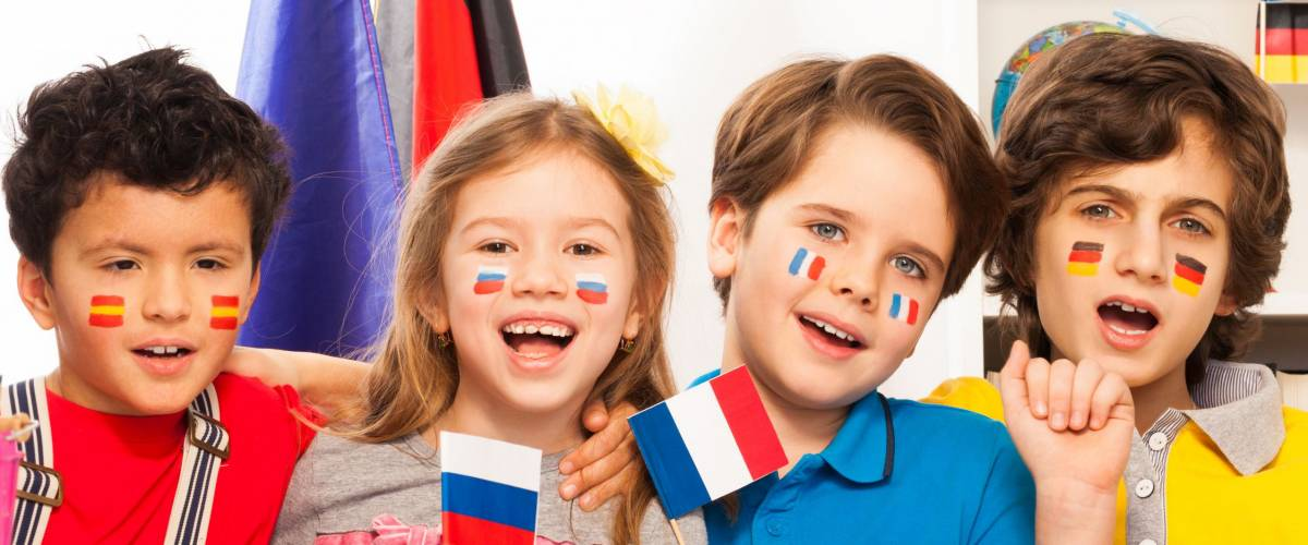 Kids with flags on cheeks singing at the classroom