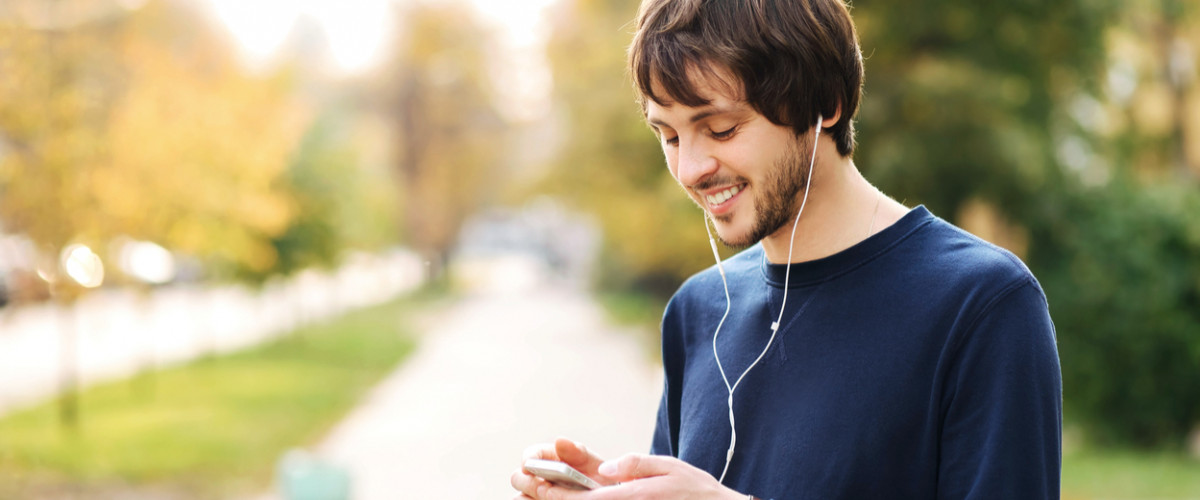 Happy young man walking and using a smart phone to listen music with headphones on street urban background