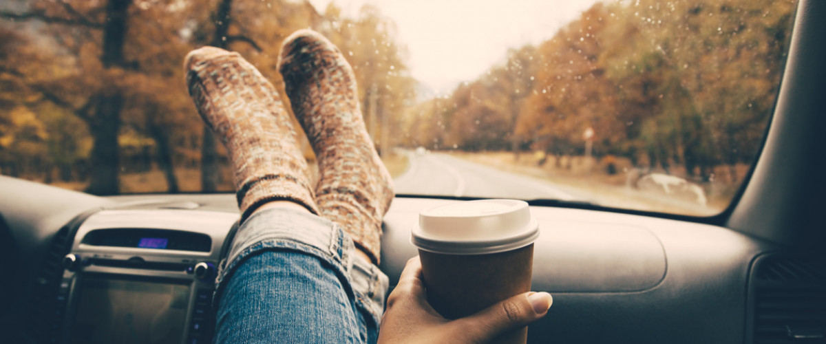 Woman feet in warm socks on car dashboard. Drinking take away coffee on road.