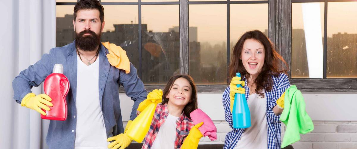 Family clean house. Happy family hold cleaning products. Mother, father and daughter clean house.
