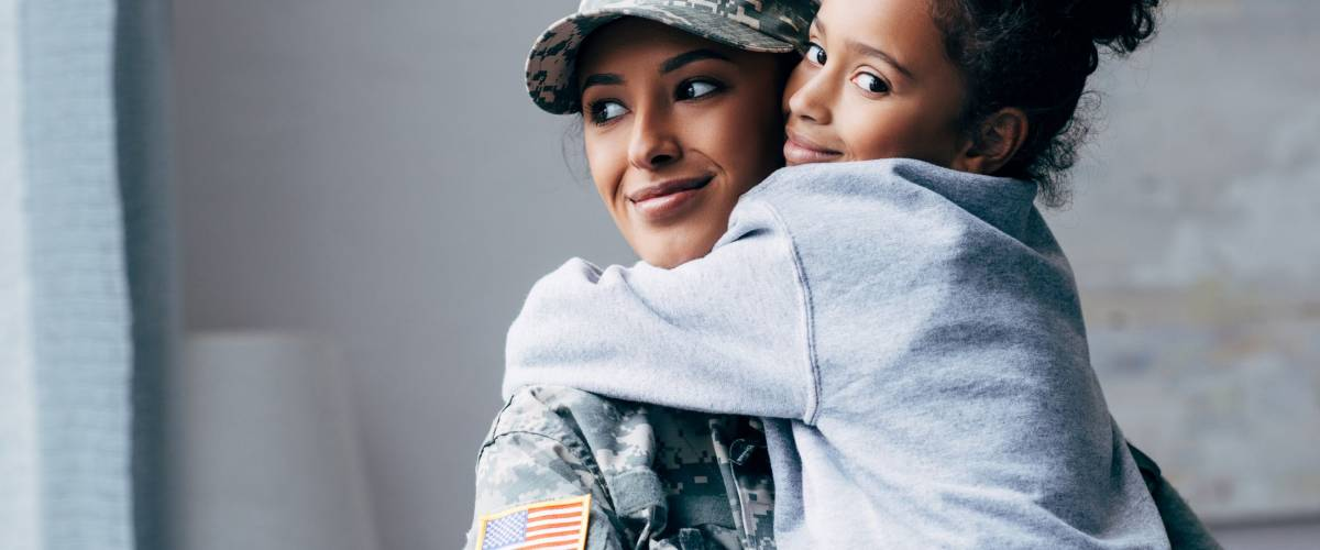 smiling african american soldier in military uniform holding daughter on arms at home