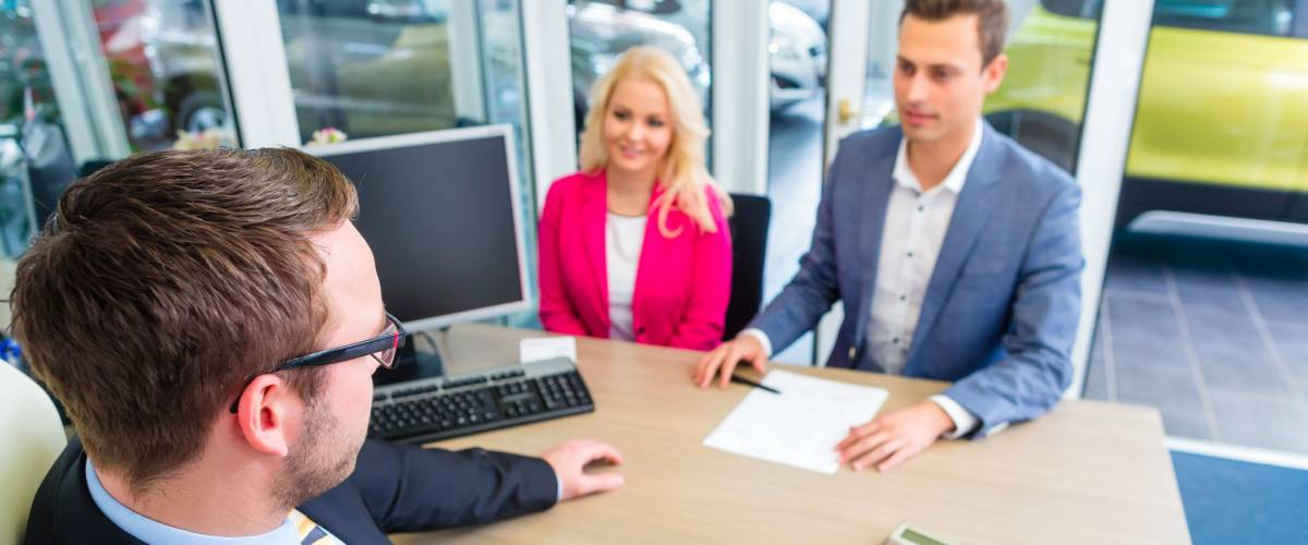 Couple buying car at dealership and negotiating price with salesman