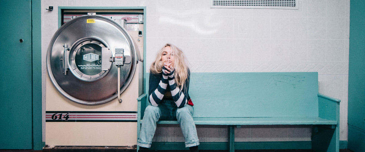 Young woman waiting for her laundry to finish in an old laundromat