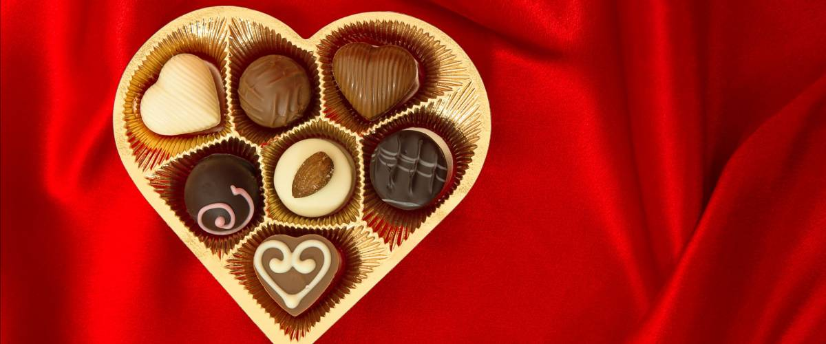 chocolate pralines in golden heart shape box over red silk background