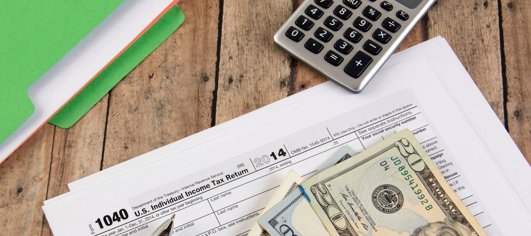 Filing federal taxes for a refund - tax form currency and calculator ona wooden bench