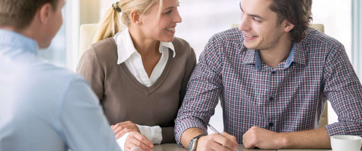 smiling young couple signing an agreement in the presence of a broker