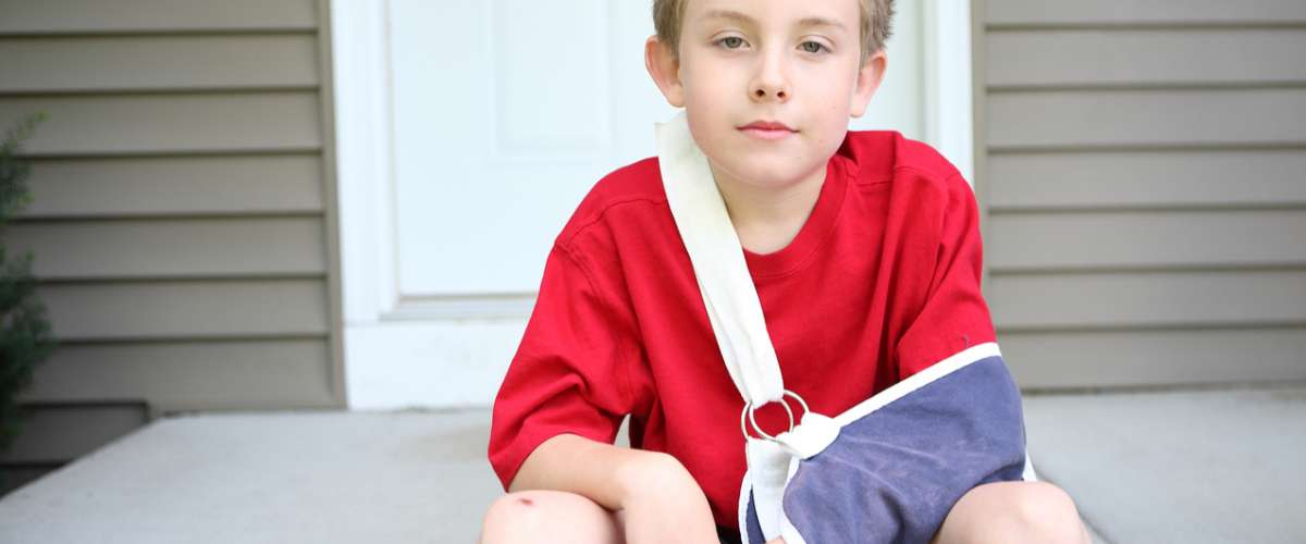 Boy with broken arm in a sling and cast