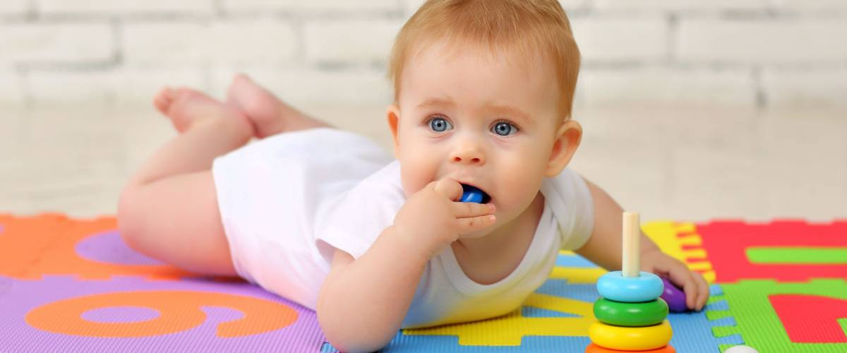 A 7-month-old baby plays on the floor with toys and stuffs small parts into his mouth