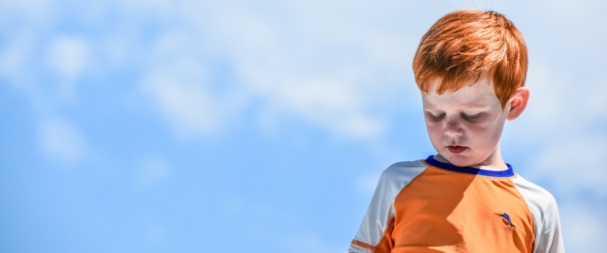 Red headed boy standing against a blue sky