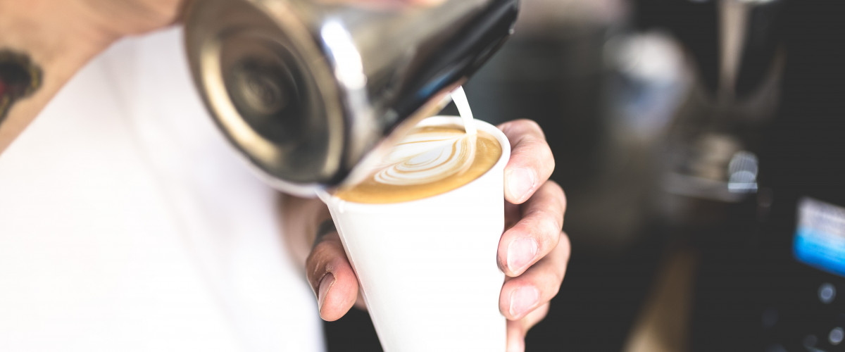 Barista making a latte in a coffee shop