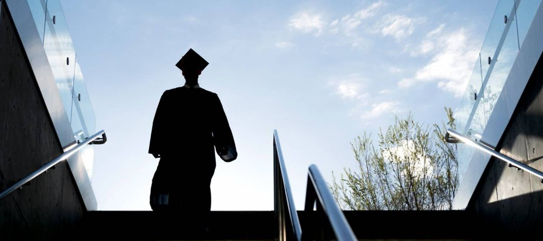 College graduate in silhouette wearing cap and gown and descending a stairway into a subway or underground garage