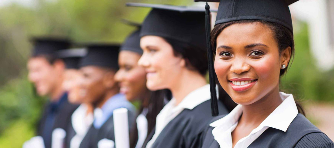 pretty african female college graduate at graduation with classmates