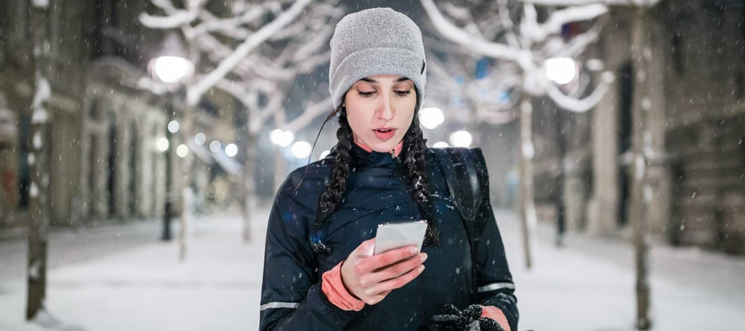 Woman checks her credit score on her smartphone while a light snow falls