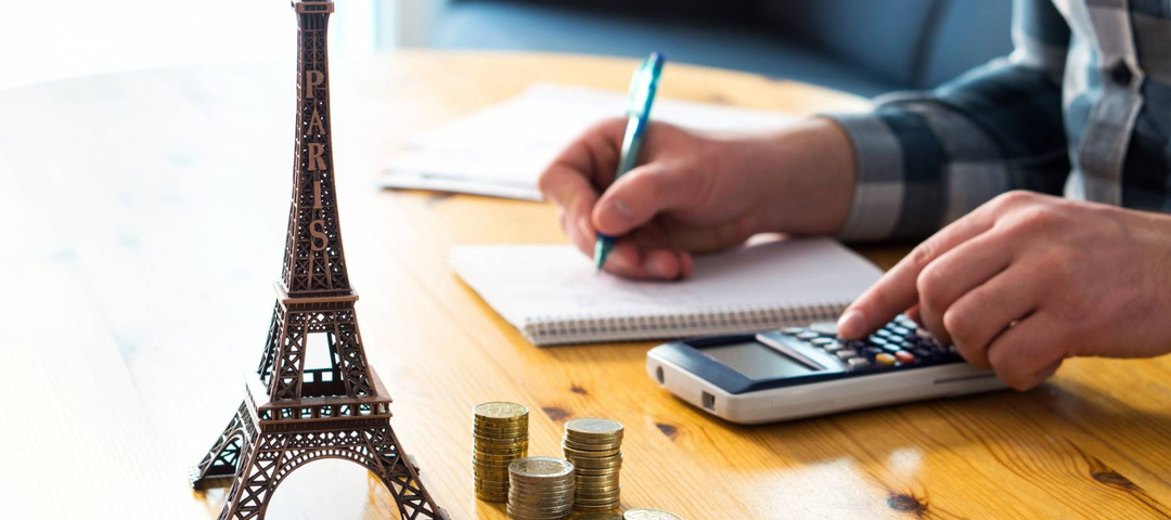 Man counting travel budget, vacation expenses or insurance cost. Traveler planning holiday in Europe. Cheap flights and hotel. Money and little Eiffel Tower souvenir from Paris on table.